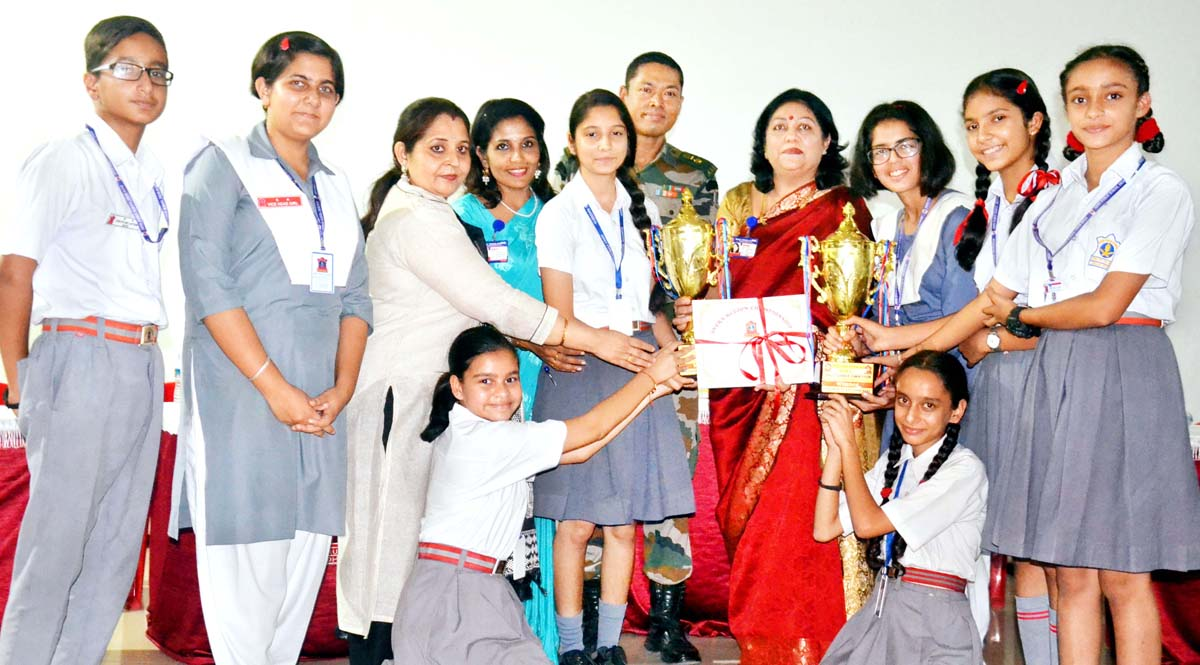 Winners of Inter-School Debate Competition posing for a group photograph at APS Dhar Road in Udhampur.
