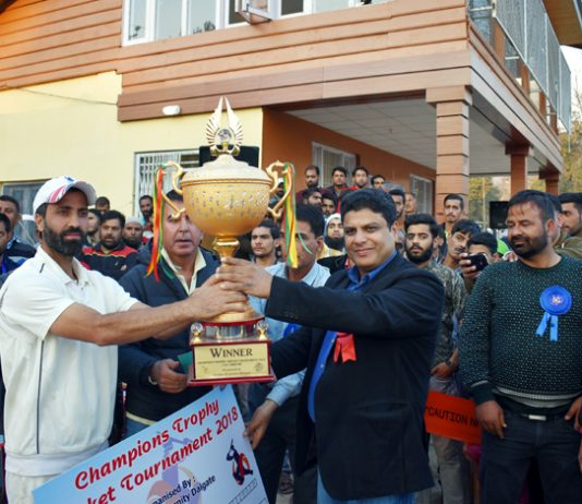 Winners of Cricket Tournament being presented a trophy by the chief guest Sarmad Hafeez in Srinagar.
