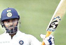 Rishabh Pant raises his bat after completing his half-century.
