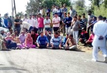 Villagers blocking Bantalab-Gharota road at Kaink Morh in Jammu.