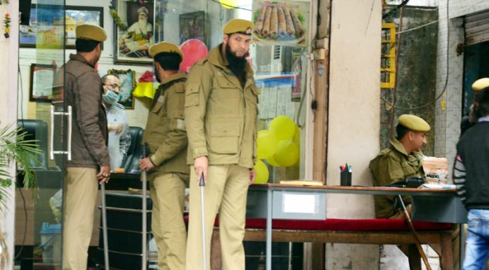 Police deployed outside the establishment of a fish wholesaler in Gummat area of Jammu during IT survey on Wednesday. —Excelsior/Rakesh