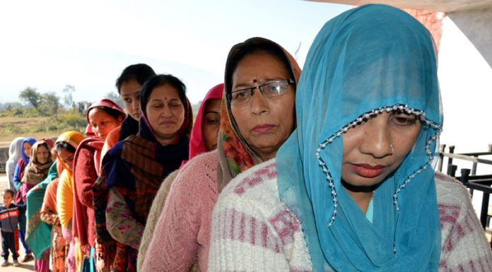 Women queue up outside a polling station in Udhampur on Saturday.