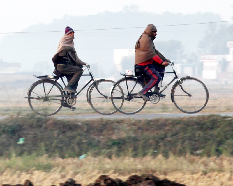 Villagers ride on bicycles heading for work on a foggy morning in Jammu on Tuesday. —Excelsior/Rakesh