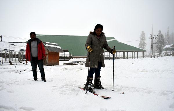Tourists enjoy fresh snowfall in Gulmarg on Friday. -Excelsior/Aabid Nabi