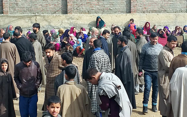 People wait outside a polling booth in Lolab, Kupwara for casting their votes on Thursday. —Excelsior/Aabid Nabi