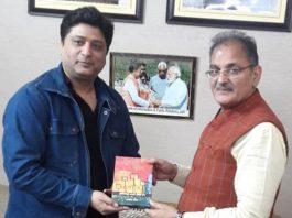 Ashish Kaul, author of the book 'Refugee Camp' presenting a copy of the book to former Deputy CM, Kavinder Gupta.