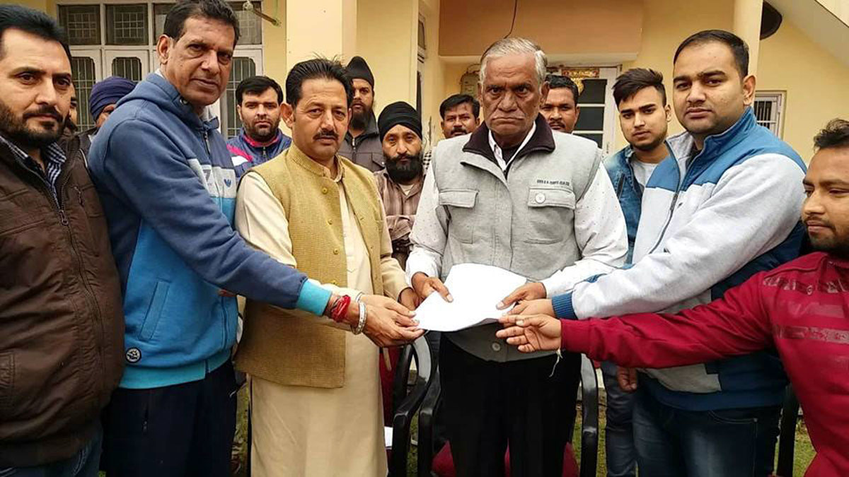 BJP Jammu district President and Corporator, Baldev Singh Billawaria handing over letters to beneficiaries under Housing for All scheme at Jammu on Thursday.