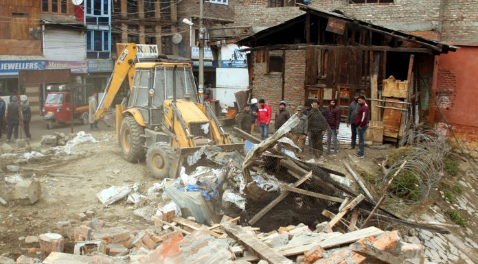 Authorities removing a CRPF bunker after 30 years in Amirakadal area of Srinagar on Tuesday. -Excelsior/Shakeel