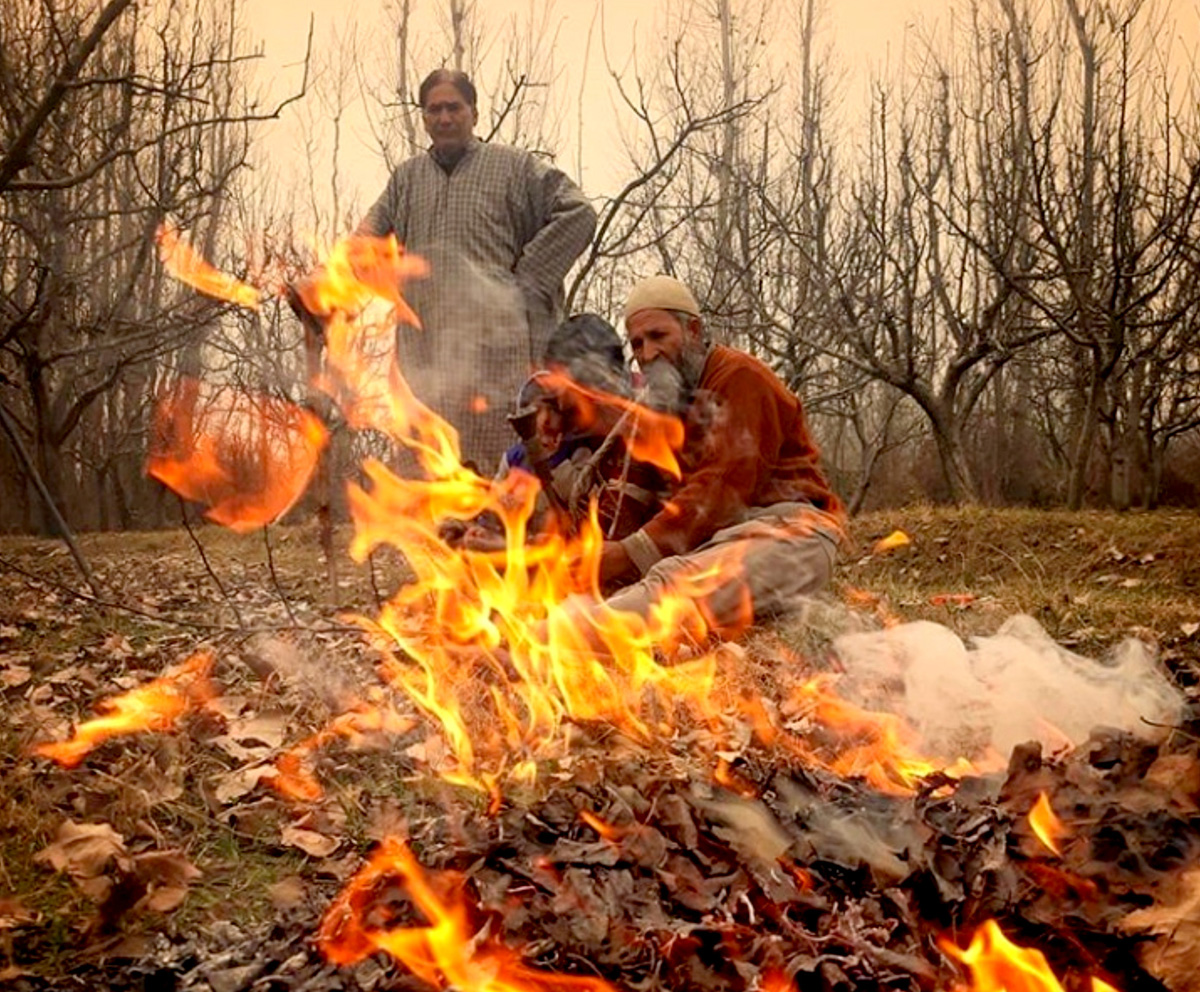 A group of people warm themselves near a bonfire on the outskirts of Srinagar on Sunday. —Excelsior/Shakeel