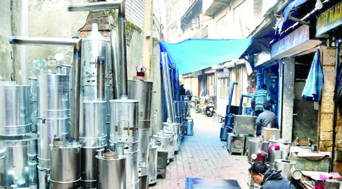 As cold tightens its grip in Valley, a shopkeeper is busy in making heating appliances locally called 'Bukhari' in Srinagar on Tuesday. -Excelsior/Shakeel