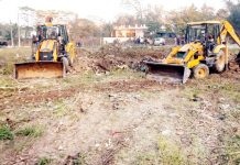 Machines removing encroachments from a pond in Kathua town on Tuesday. -Excelsior/Pardeep