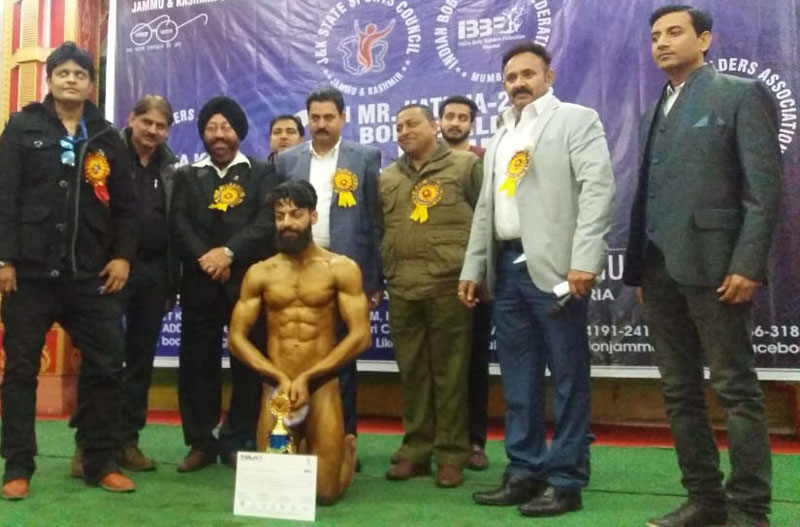 Shivam Sehdev posing along with dignitaries and officials after winning champion of champions award in District Kathua Body Building Championship.