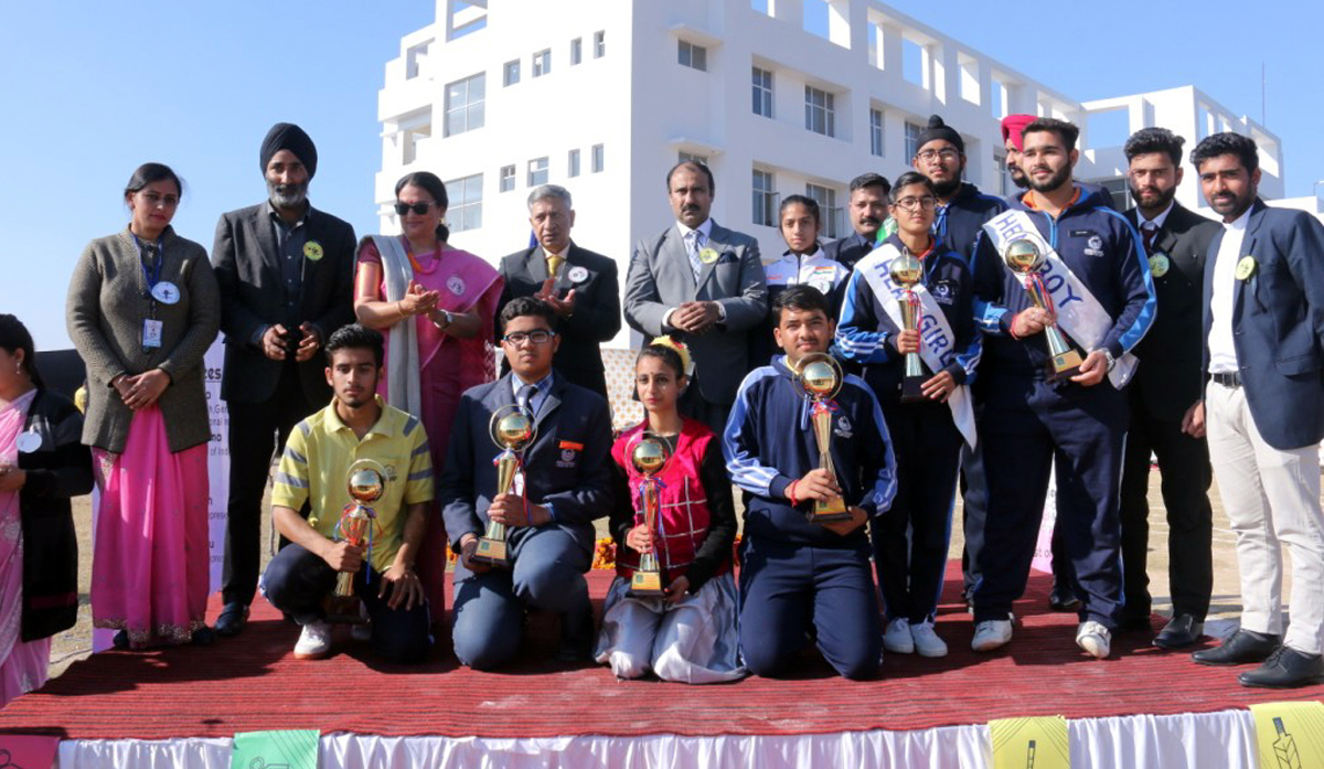 Winners of various games posing with trophies and medals along with chief guest and other guests.