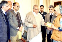 Governor Satya Pal Malik giving away cheque to kin of deceased ASHA worker at Raj Bhavan on Monday.