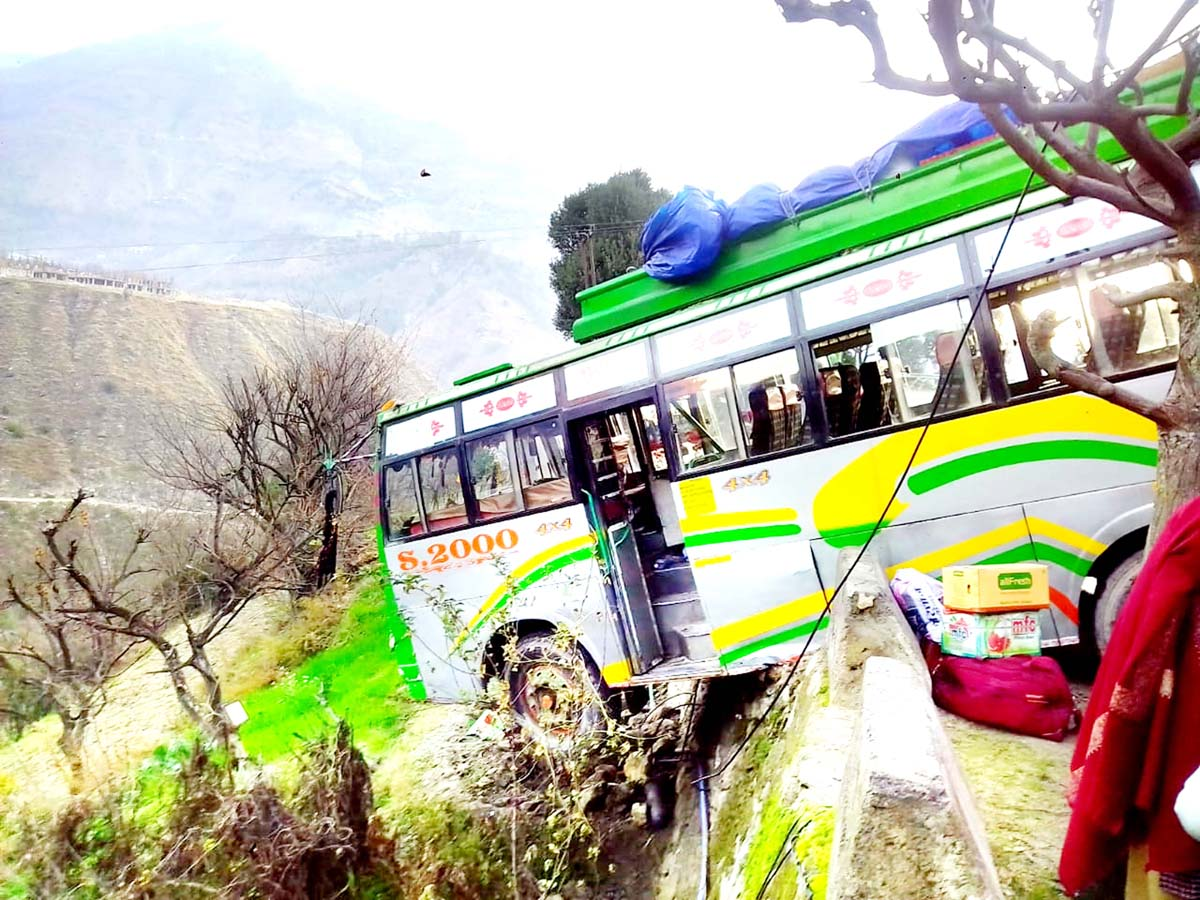 A bus hangs from edge of hill road.