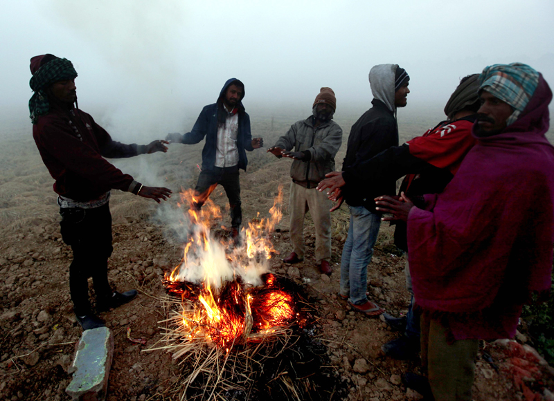 Villagers lit fire to have some relief from chilling cold on outskirts of Jammu on Saturday morning. -Excelsior/Rakesh