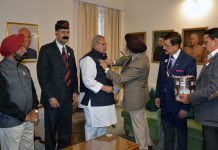 Director Rajya Sainik Board pinning Governor Satya Pal Malik with flag during Armed Forces Flag Day in Jammu on Friday.