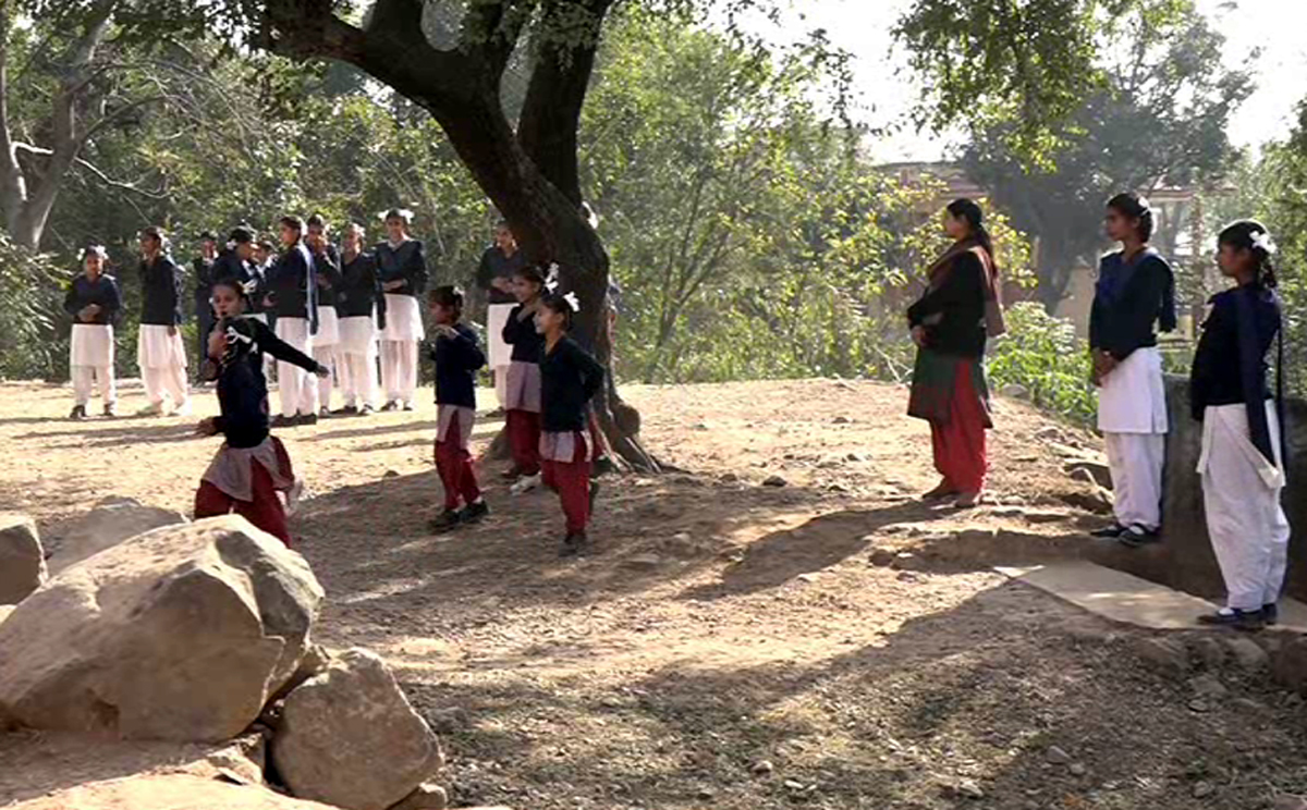 Students playing in open under supervision of teachers as school sans boundary wall.