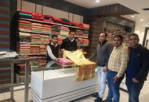 Salesmen showing a fashion wear to a customer at newly opened showroom of Yougal Sons at Dogra Chowk, Jammu.