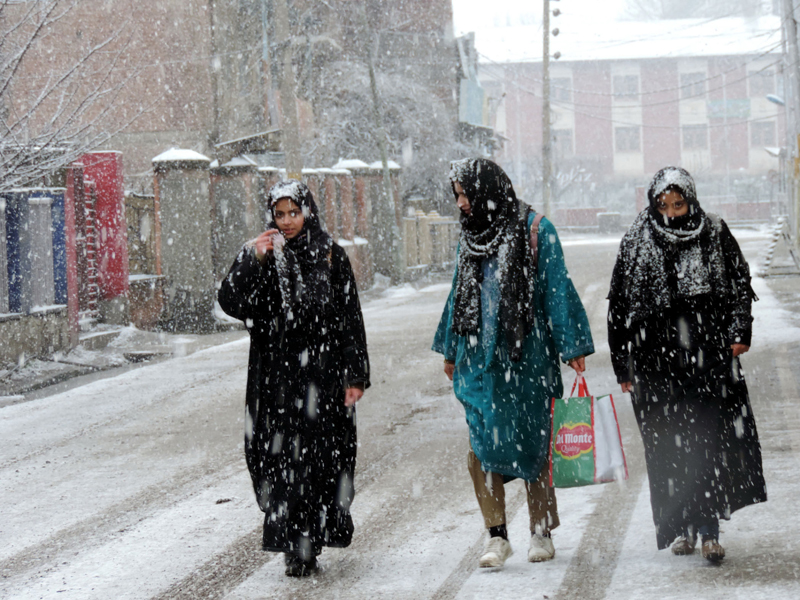 Women walking down a street amid snowfall in Srinagar on Thursday. (UNI)