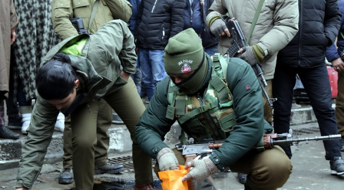 Security personnel collect splinters after grenade blast in Lal Chowk, Srinagar on Friday. -Excelsior/Shakeel