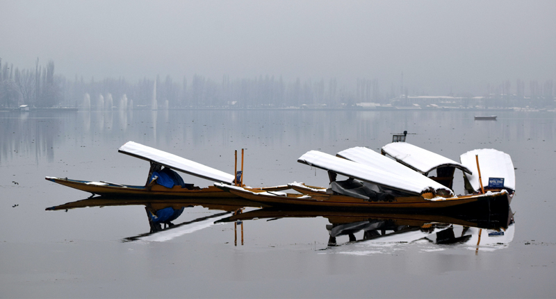 Snow covered shikara boats pictured in Dal lake after fresh snowfall. -Excelsior/Shakeel