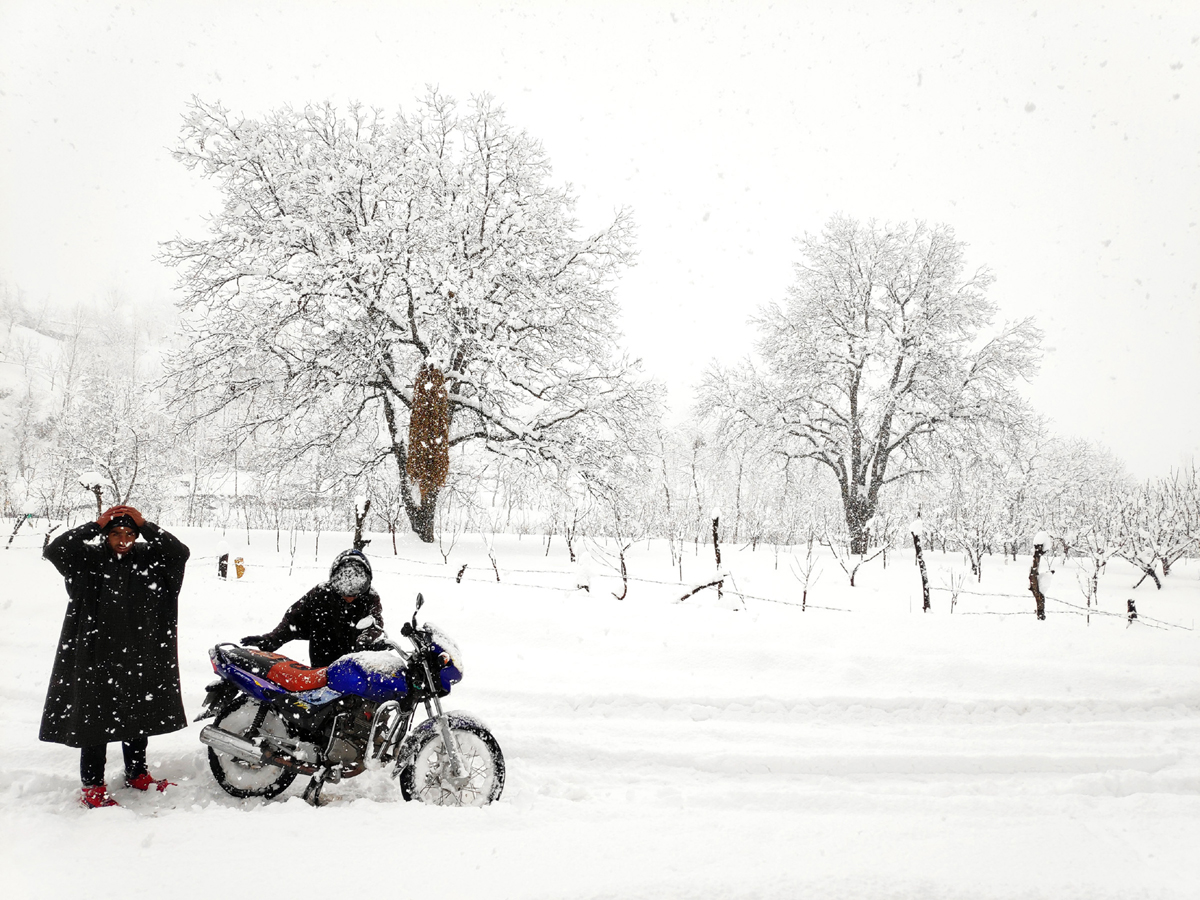 A motorcyclist tries to move his bike amid heavy snow in Pakherpora area of Budgam district on Monday. -Excelsior/Younis Khaliq