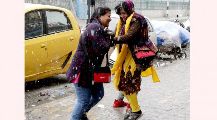 Girls enjoy snowfall in Srinagar on Friday. -Excelsior/Shakeel