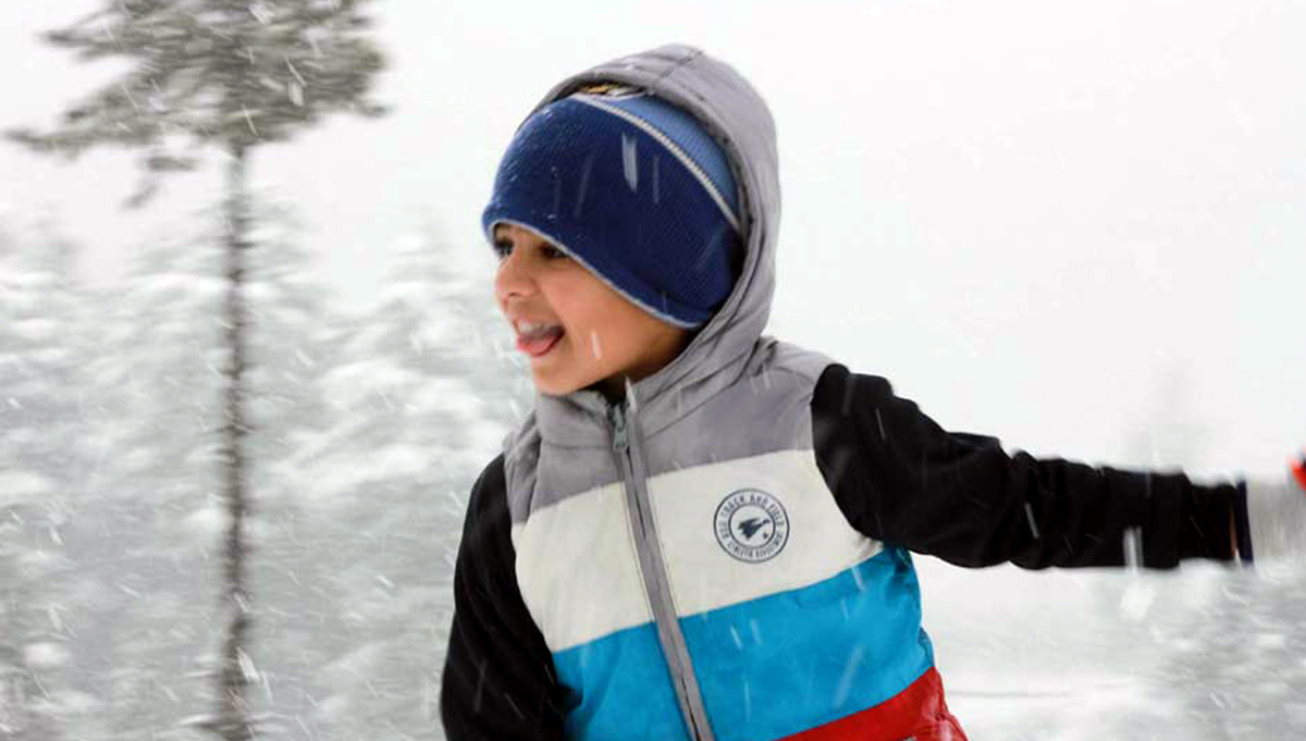 A child plays during snowfall as higher reaches in Bhaderwah valley witness fresh snowfall on Monday. (UNI)