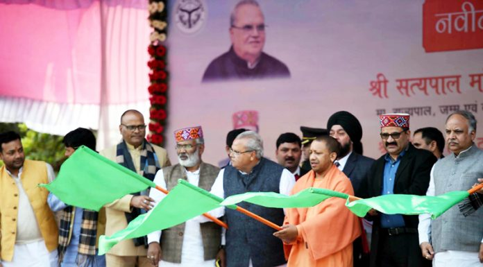 Governor Satyapal Malik, UP Chief Minister Yogi Adityanath and Transport Minister of HP Govind Singh Thakur flagging off a bus outside residence of UP Chief Minister in Lucknow on Monday. (UNI)