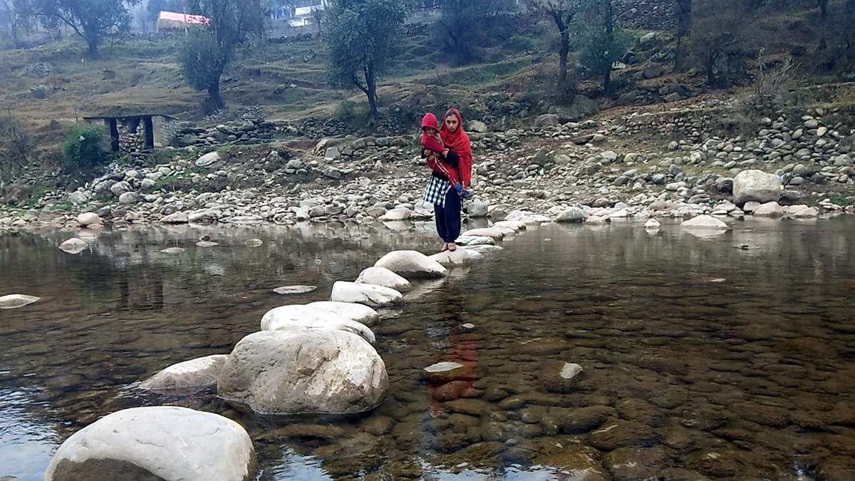 A villager passing through river in the absence of bridge near Darana village in Mendhar. —Excelsior/Rahi Kapoor