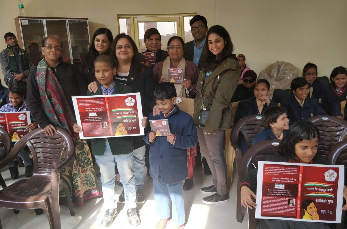 Nupur Sandhu posing with visually impaired children carrying audio-book 'Bharat Ke Bahadur Bachche'.