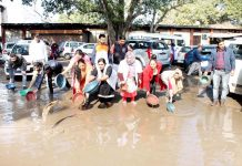 NHM employees removing water stagnated in front of Press Club Jammu during their ongoing protest on Wednesday. -Excelsior/Rakesh