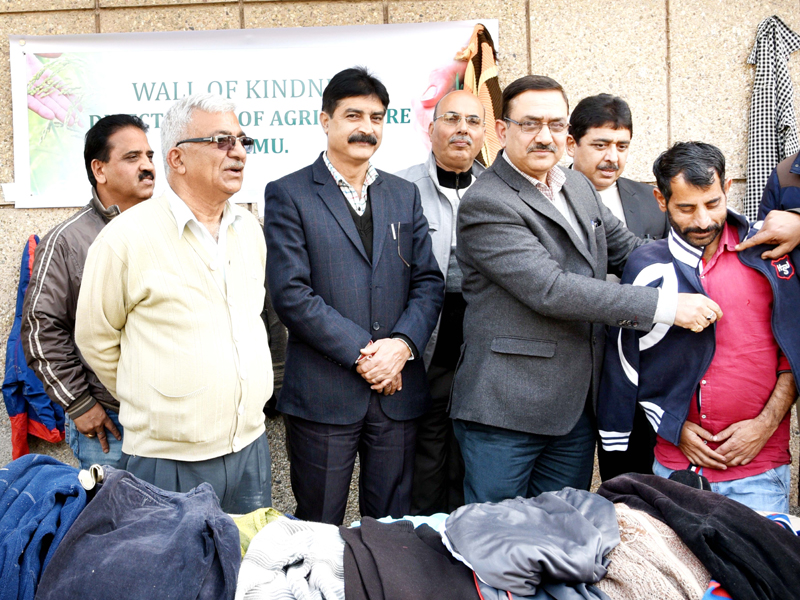 Director Agriculture HK Razdan presenting clothing item to a needy person during week long
