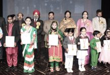 Students in colourful attires posing along with dignitaries during Annual Day celebration at Dogra HSS Shastri Nagar in Jammu.