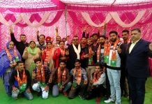 Former Minister and senior BJP leader, Chander Parkash Ganga, posing with new entrants of the party at village Jhar of Ramgarh block in Samba district.