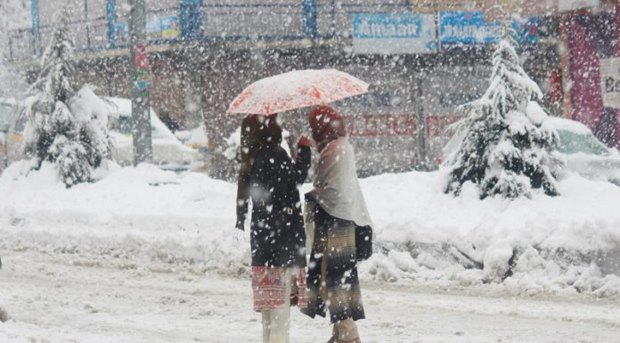 Two women braving snow while moving on road holding umbrella in Baramulla area on Wednesday. —Excelsior/Aabid Nabi