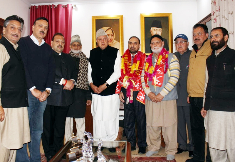 NC President Dr Farooq Abdullah posing for group photograph with new entrants in party fold on Thursday.