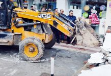 Encroachment being removed with the help of JCB at Udhampur town on Friday.