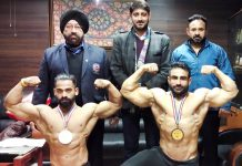 Ajeet Singh Jamwal and Deepak Sharma displaying muscles while posing for a photograph along with officials.