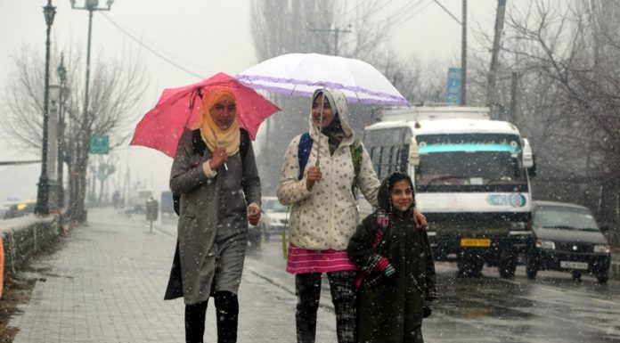 People walk amid fresh snowfall in Srinagar on Thursday. -Excelsior/Shakeel