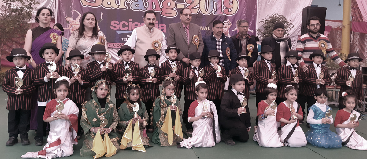 Children in colourful attires posing along with dignitaries by celebrating Sarang 2019 at Scientia International School in Jammu.