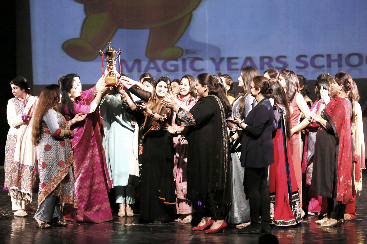 A trophy being lifted by the students and the staff during Annual Day function of Magic Years School.