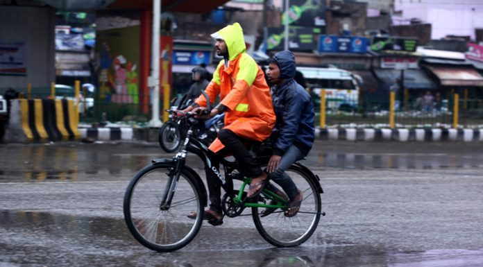 Cyclists brave early morning rains in Jammu on Monday. -Excelsior/Rakesh