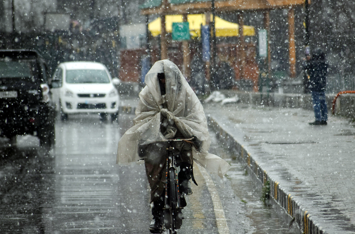 A cyclist moves on a Srinagar road amid snowfall on Wednesday. —Excelsior/Shakeel