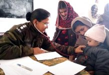 A doctor examining patients during medical camp at Balakote near LoC.