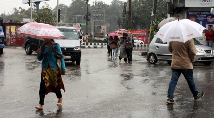 People holding umbrellas move through Jammu roads on rainy Monday. -Excelsior/Rakesh