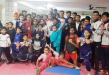Young sportspersons posing for a group photograph during inaugural function of State Wushu Championship in Jammu.