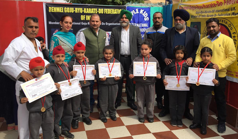 Children holding certificates while posing for a photograph during Belt Grading Test at Apple Kids Pre-School in Jammu.