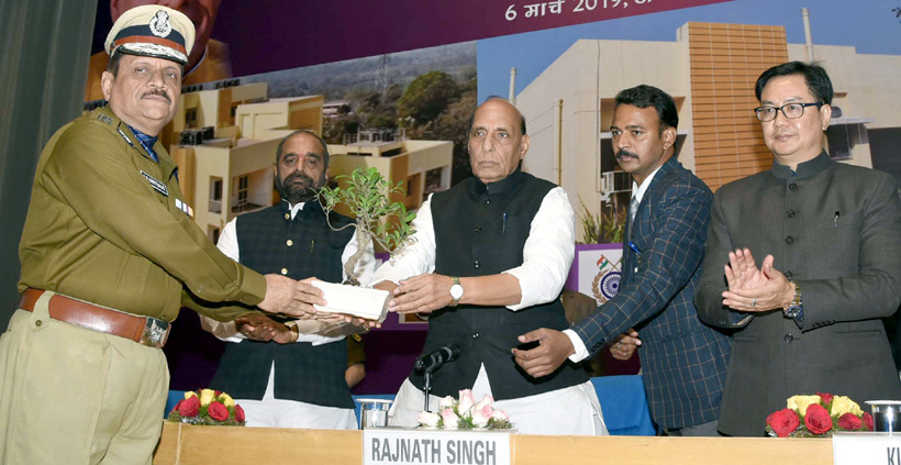 Union Home Minister, Rajnath Singh being greeted by the DG, CRPF, Rajeev Rai Bhatnagar with a sapling, at the inauguration and foundation stone laying ceremony of various residential and office buildings of CAPFs, CPOs and Delhi Police, in New Delhi on Wednesday.
